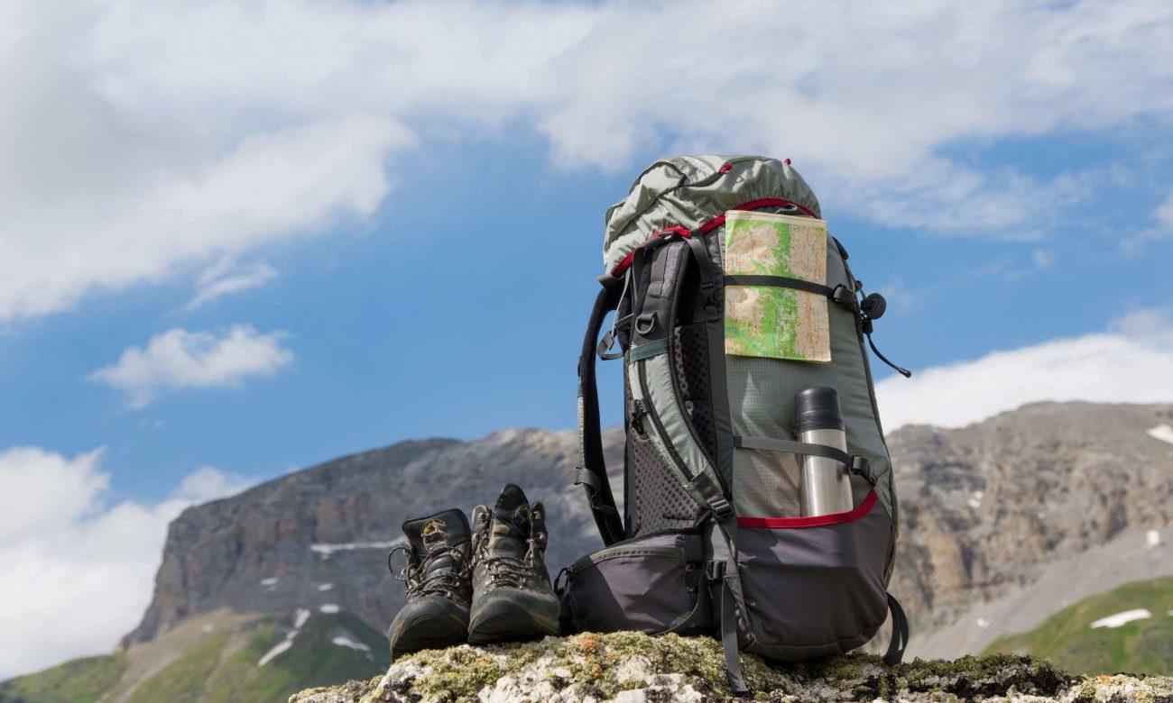 Bild zum Blogbeitrag, das Rucksack und Berge im Hintergrund zeigt